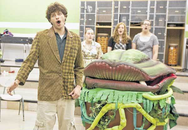 "Standing next to the carnivorous plant, Brady Lesh, playing Seymour, sings during a rehearsal for ""Little Shop of Horrors"" at Marian High School."