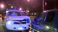 Two Chicago police officers were injured when someone plowed into their marked police SUV while they took a police report from someone they had in their back seat Sunday morning.