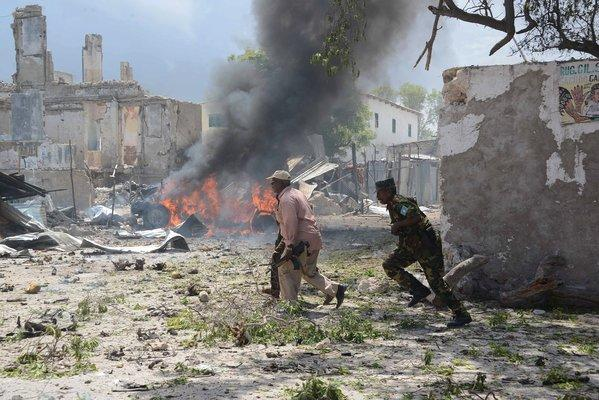 Somali police run for cover Sunday after gunmen wearing suicide vests stormed the main court complex in Mogadishu and took hostages.