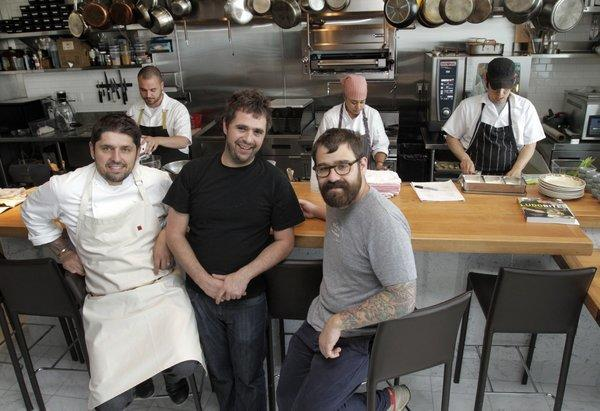From left, Ludo Lefebvre (chef-co-owner), Vinny Dotolo (co-owner) and Jon Shook (co-owner) of the new Trois Mec restaurant with the kitchen staff behind them in the restaurant.