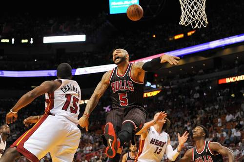 Carlos Boozer is fouled by the Heat's Mario Chalmers during the first half.