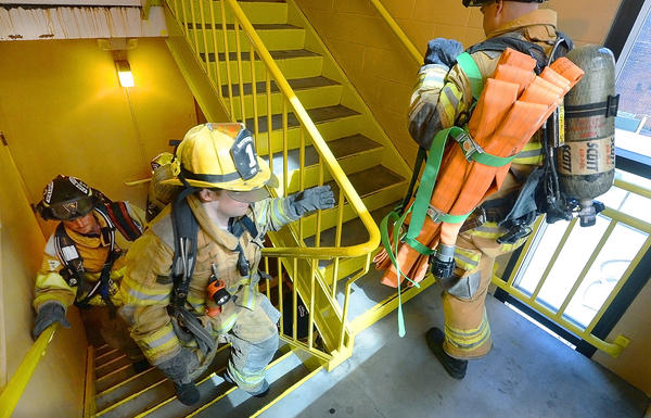 Hagerstown Fire Department firefighters Cole Hollinger, left, Zachary Schmidt and Scott Wolff climb five floors of stairs to the North Potomac Street Parking Deck during a training exercise Sunday.