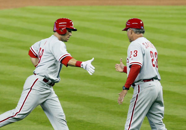 Apr 14, 2013; Miami, FL, USA; Philadelphia Phillies left fielder Laynce Nix (19) gets congratulations from third base coach Ryne Sandberg (23) for his pinch hit home run in the ninth inning against the Miami Marlins at Marlins Park. The Phillies won 2-1. Mandatory Credit: Robert Mayer-USA TODAY Sports ORG XMIT: USATSI-120664