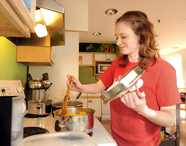 McDaniel College student Megan Loudon, 21, stirs Spanish rice. She is part of Heroes Helping Hopkins, an on-campus group that cooks meals for families at the Believe in Tomorrow Children's House.