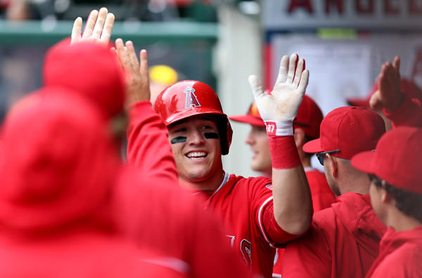 Angels teammates congratulate Mike Trout after he scored a run against the Astros on Sunday afternoon in Anaheim.