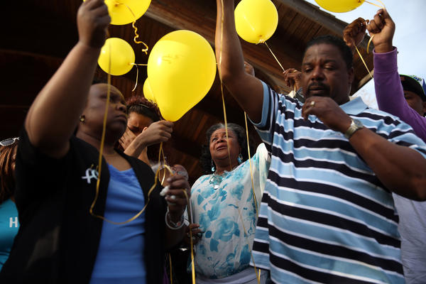 Cynthia Mackins (center), the sister of missing Joliet woman Jeanie Parker, takes part in a balloon launch during a prayer vigil for Parker at Bicentennial Park in Joliet on Sunday. Parker's son, Charles McCullum, was charged with the murder and is being held on $5 million bond. A body that may be Parker's was found in the Des Plaines River by fishermen.