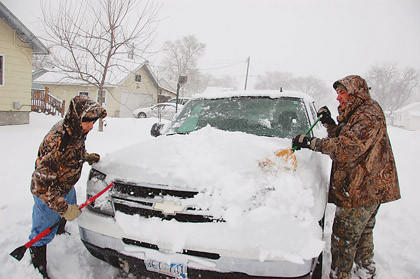 "Justin Boynton, left, and Matt Ragels clean snow off a car Sunday afternoon. The two had just returned from turkey hunting in Mobridge and were surprised to see so much snow. ""Now it's time to begin shoveling,"" Ragels said."