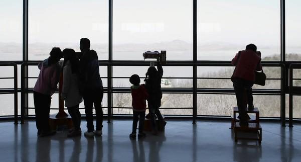 A family looks at North Korean territory from an observation post near the border village of Panmunjom, South Korea. Weeks of shrill rhetoric from North Korea, preceded by a nuclear test in February, have put U.S., South Korean and Japanese forces on high alert.