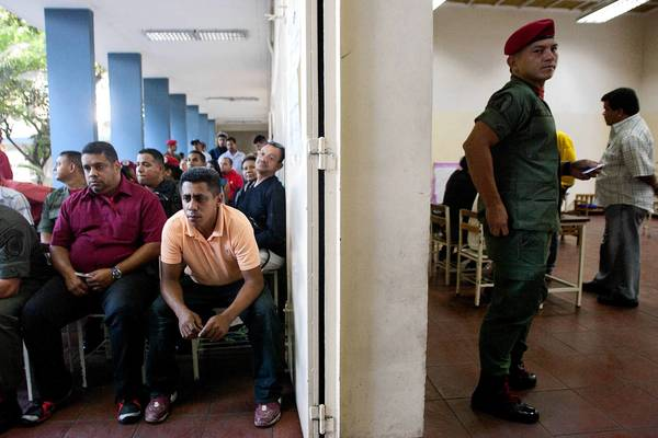 Venezuelans line up to vote in Caracas as a member of the National Bolivarian Armed Forces keeps watch.