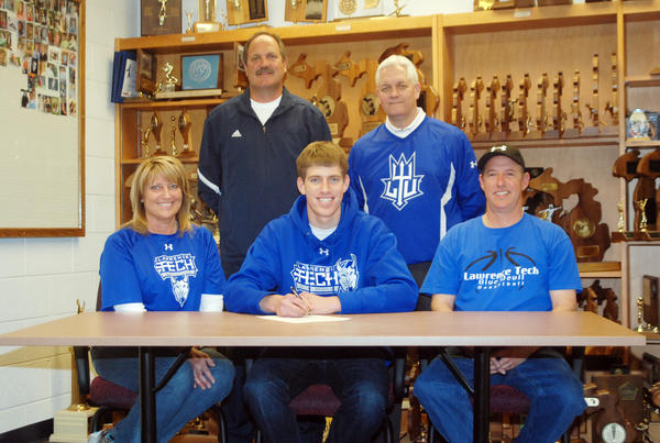 Petoskey High School senior Erik Davenport (front, center) signs his national letter of intent to play college basketball at Lawrence Technological University (Southfield) Thursday at the Petoskey High School athletic office. Joining Davenport at his signing is (from left) his mother Helen Davenport, Petoskey High School boys basketball coach Dennis Starkey, Lawrence Tech mens basketball coach Tom Kempf and father Jim Davenport.