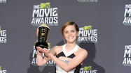 "Emma Watson seemed poised and looked elegant as she accepted the Trailblazer award at the 2013 MTV Movie Awards Sunday in Culver City. She stood out at an event where, as my colleague Glenn Whipp writes, many of the stars seemed to use the Macklemore song ""Thrift Shop"" as a dressing inspiration. That seemed especially true of the men. (Taylor Lautner seemed to be bursting out of his too-small shirt as he accepted for Best Shirtless Performance -- but that was probably on purpose, of course. What excuse did some of the others have?) <a href=""http://www.latimes.com/entertainment/envelope/goldstandard/la-et-mn-mtv-movie-awards-20130414,0,1851985.story"">[Los Angeles Times]</a>"
