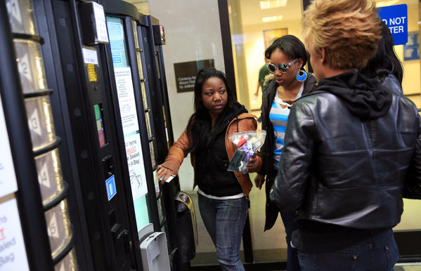 Alicia White retrieves her cellphone from the storage vending machine at the Leighton Criminal Court Building.
