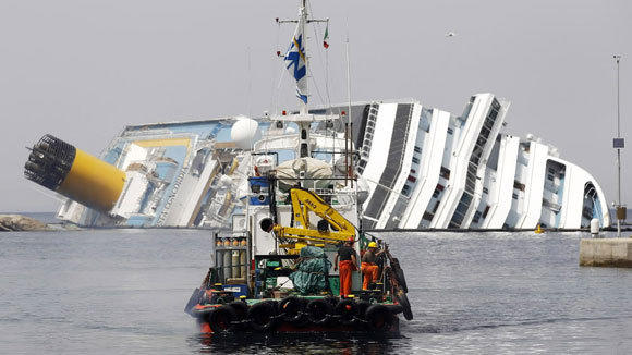 A boat with rescue workers sails in front of capsized cruise liner Costa Concordia near the harbor of Giglio Porto on June 20, 2012.