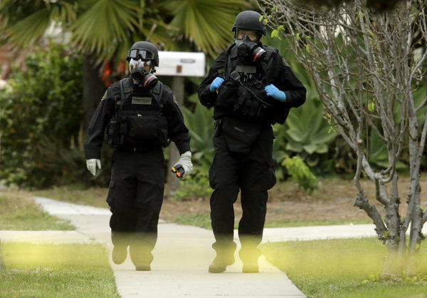 Orange County Sheriff's Department bomb squad members walk away from a home on Bermuda Drive in Costa Mesa where a 52-year-old man apparently committed suicide with an explosive device.