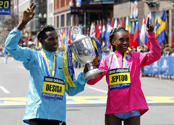 The 117th Boston Marathon men's division winner Lelisa Desisa Benti, of Ethiopia, (L) and women's division winner Rita Jeptoo of Kenya pose for a portrait with the trophy.