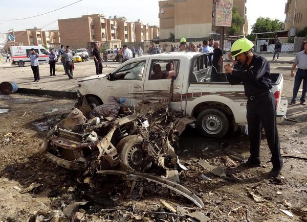 An Iraqi policeman inspects the site of a car bomb attack in Kirkuk.