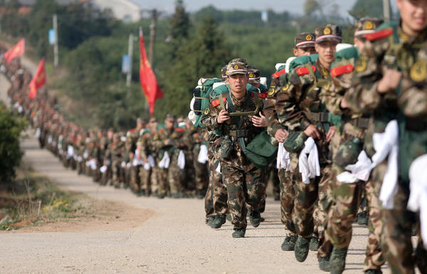 Chinese paramilitary police recruits run on a village road as they take part in field training in Hubei province.