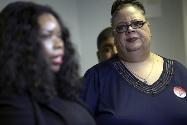 Chicago Teachers Union president Karen Lewis, right, listens as teachers describe conditions at an elementary school before it was listed for closing.