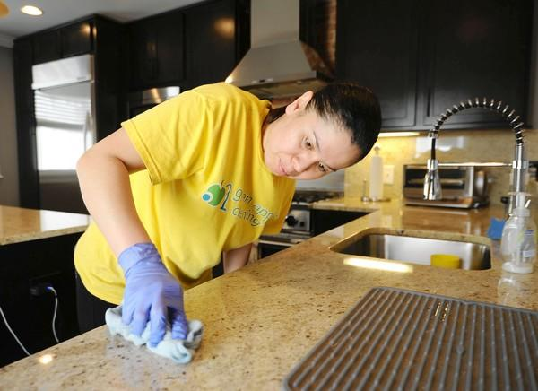 Keyla Paz with Green Apple Cleaning crew cleans one of the kitchen counters in a home on Highland Avenue in Canton.