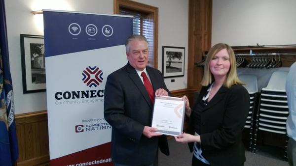 Tom Stephenson, community technology advisor for Project Connect, hands Rachel Smolinski, executive director of HARBOR, Inc., a certificate showing the completion of the Harbor Springs Technology Action Plan.