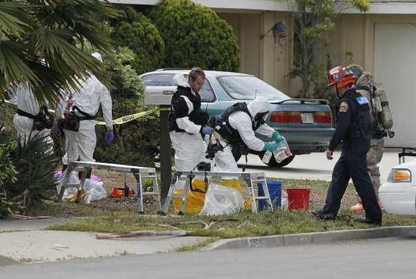 Bomb squad personnel bag up materials from inside a home at 3152 Bermuda Drive in Costa Mesa on Monday. A man who identified himself as Kevin Harris in an online manifesto, apparently blew himself up on Sunday evening.