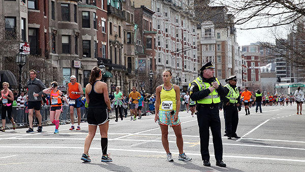 Police and runners stand near Boston's Kenmore Square after two explosions during the 117th Boston Marathon on Monday.