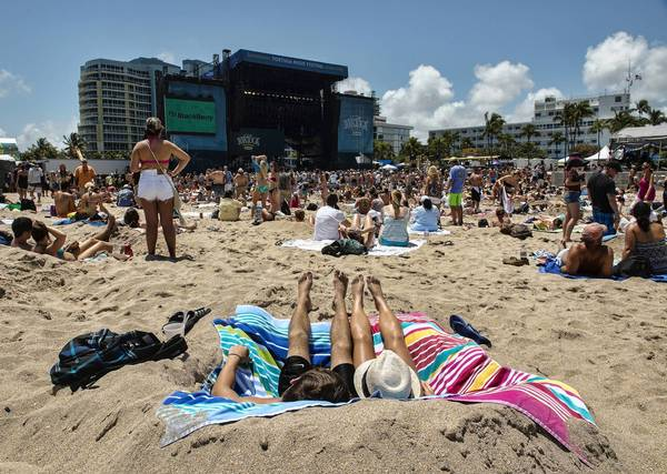 "Concert goers listen to the band as they sit along the beach in Fort Lauderdale during Rock the Ocean's ""Tortuga Music Festival""."