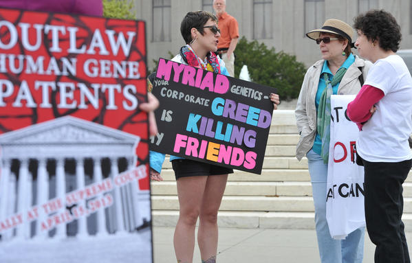 Protesters hold banners demanding a ban on the patenting of human genes outside the Supreme Court in Washington on Monday.