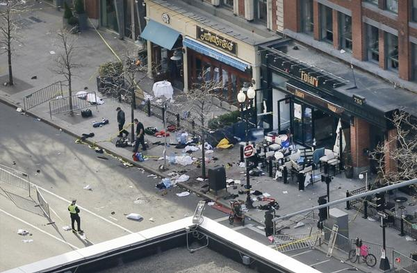 One of the blast sites on Boylston Street near the finish line of the Boston Marathon is investigated and guarded by police.