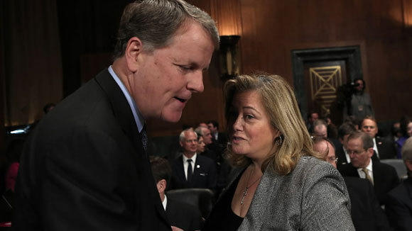 Doug Parker, CEO of US Airways, talks to lobbyist Hillary Rosen before a hearing of the Senate Judiciary Committee March 19.