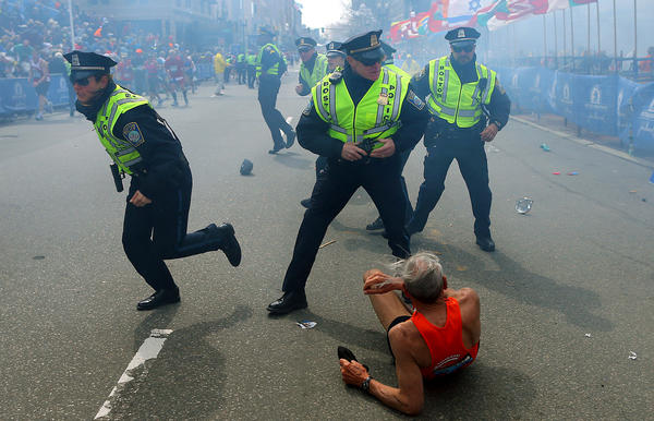 Police officers react to the second of two explosions near the finish line of the Boston Marathon.