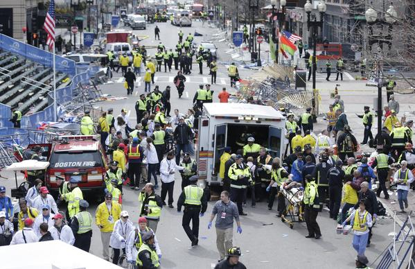 Medical workers aid injured people Monday at the finish line of the Boston Marathon following explosions.