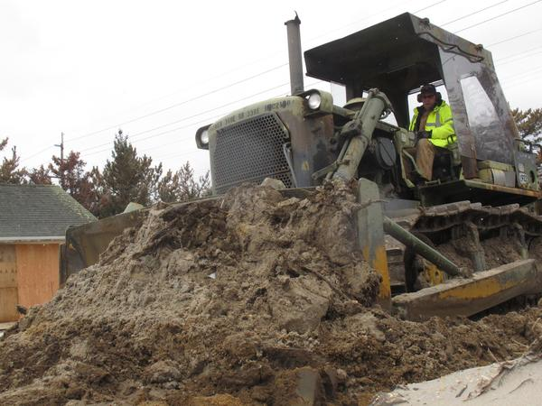 The federal government spent about $150 billion on relief efforts after Hurricane Katrina, and has so far committed about $60 billion for Superstorm Sandy. Above: A public works employee uses a bulldozer to rebuild a sand dune in Mantoloking N.J. that was washed away by a lingering winter storm that caused flooding and other damage at the Jersey shore, parts of which are still struggling to recover from Superstorm Sandy.