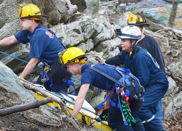 Rescue workers scale treacherous and rocky terrain Monday as they carry the body of a man who fell to his death.