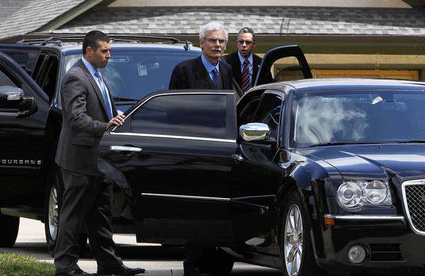 Tom Smedinghoff, whose daughter Anne was killed this month in Afghanistan, is accompanied by Secret Service members Monday as he and his family leave their River Forest home to meet with Secretary of State John Kerry.