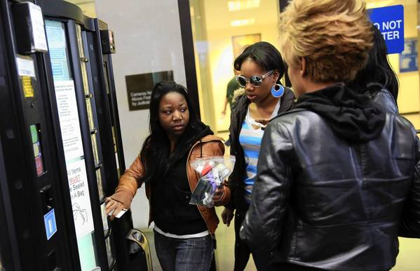 Alicia White, right, retrieves her cellphone from a storage vending machine Monday at the Leighton Criminal Court Building.