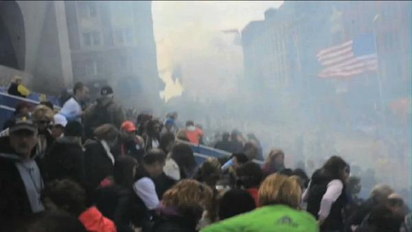 In this image from video provided by Ryan Hoyme, the second explosion can be seen in the distance as smoke from the first explosion surrounds spectators exiting the stands during the Boston Marathon.