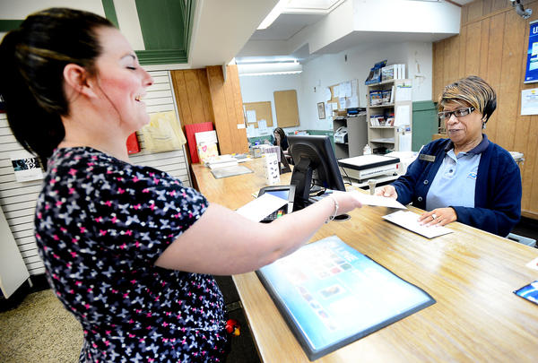 Amy Beard, left, of Clear Spring dropped off her tax return as well as the returns of a family member and a coworker at the U.S. Post Office in Hagerstown during her lunch break Monday afternoon. Taking her mail is Chrystal Kemp, lead sales and service associate.