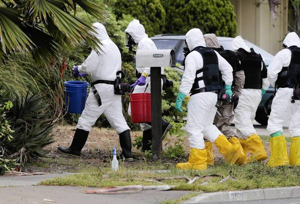 Investigators wearing hazmat suits approach the Costa Mesa home of Kevin Harris, who died in an explosion there.