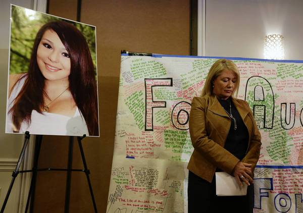 Sheila Pott, mother of Audrie Pott, the 15-year-old who committed suicide after what her family believes was a sexual assault, stands by a photograph of her daughter and a message board during a news conference in San Jose.