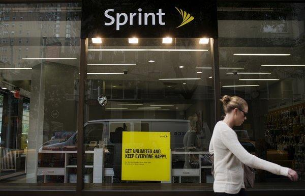 A pedestrian passes a Sprint store in New York. The wireless carrier is weighing a buyout offer from Dish Network against a previous bid by SoftBank for 70% of the company.