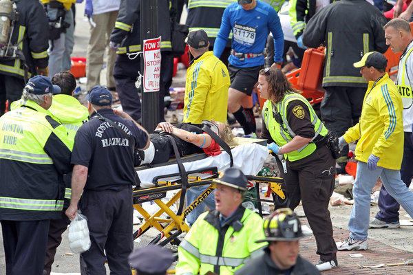 Rescue personnel aid injured people near the finish line of the 2013 Boston Marathon following explosions in Boston, Monday, April 15, 2013. Two explosions shattered the euphoria of the Boston Marathon finish line on Monday, sending authorities out on the course to carry off the injured while the stragglers were rerouted away from the smoking site of the blasts. (AP Photo/The Boston Herald, Stuart Cahill) ** Usable by LA and DC Only **