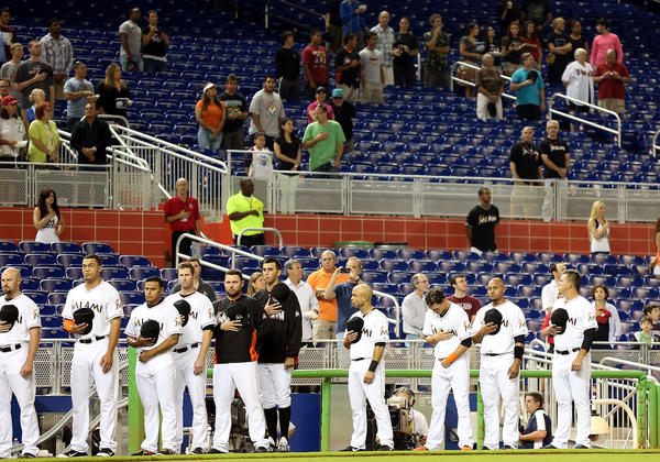 Miami Marlins players and fans stand for a moment of silence for the victims of the Boston Marathon attack prior to playing the Washington Nationals at Marlins Park in Miami.