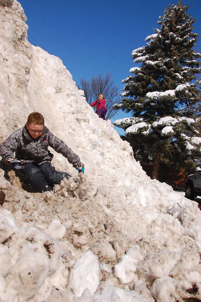 Logan Sibble, left, slides down a snow pile on Monday in Aberdeen while his sister, Skyler McLean, ascends it. Aberdeen received 11 inches of snow from the most recent snow storm, according to the Aberdeen National Weather Service.