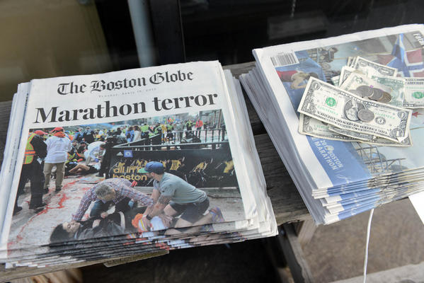 Newspapers tell the story at a stand on Newbury Street on April 16, 2013 in Boston. Security is especially tight in the city of Boston after two explosions went off near the finish of the Marathon, killing three people and injuring at least 141 others.