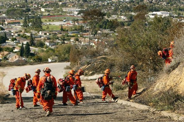 CalFire hand crews from the Department of Corrections and Rehabilitation cut brush in the mountains north of Fillmore on April 9 to get full containment of a brush fire that damaged two homes and threatened more.