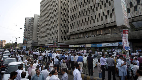 People evacuate buildings and gather on a road after an earthquake in eastern Iran on Tuesday was felt in Karachi, Pakistan. The quake was estimated to have a magnitude of at least 7.5, authorities said, but there were conflicting reports regarding any casualties.