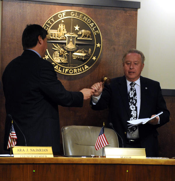 Councilman Ara Najaria, left, presents newly appointed Mayor Dave Weaver, right, with the gavel on Monday.