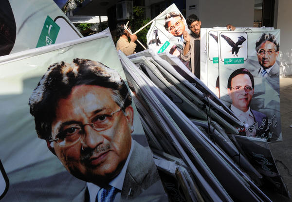 Supporters of former Pakistani President Pervez Musharraf place election banners featuring his image, foreground, at their party office in Islamabad on Tuesday.