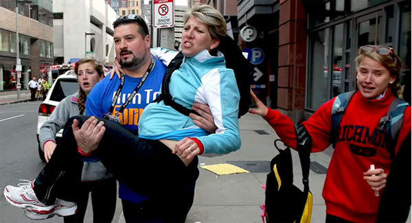 Former New England lineman Joe Andruzzi carries a woman to safety following the Boston Marathon bombings on Monday.